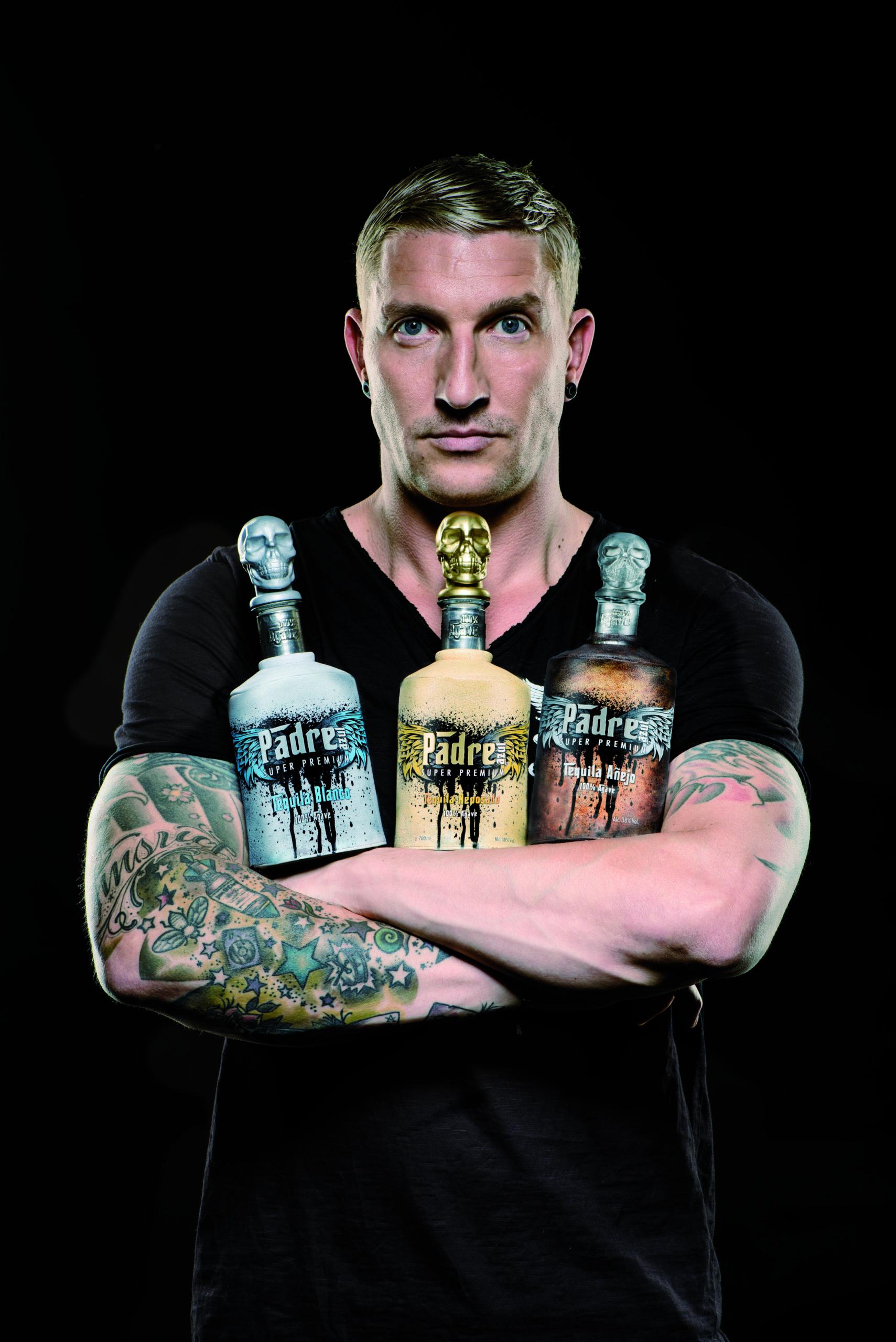 16_Kretzschmar_stehend_alle+Flaschen+im+Arm_schwarzer+Hintergrund_Hochformat